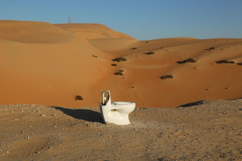 Toilet bowl on sand in desert against sky