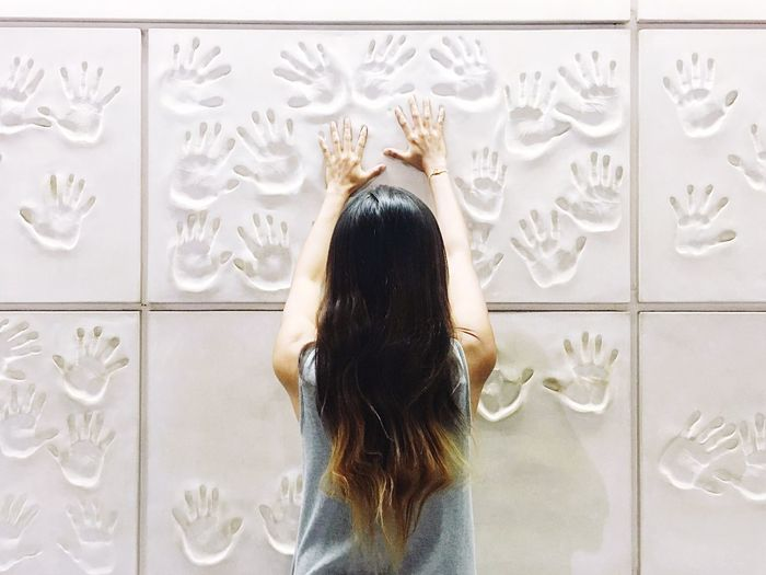 Rear view of woman touching white wall with handprints