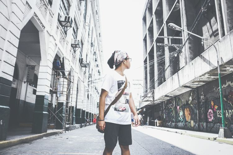 Teenage Boy Looking Away While Standing On Road Amidst Buildings In City