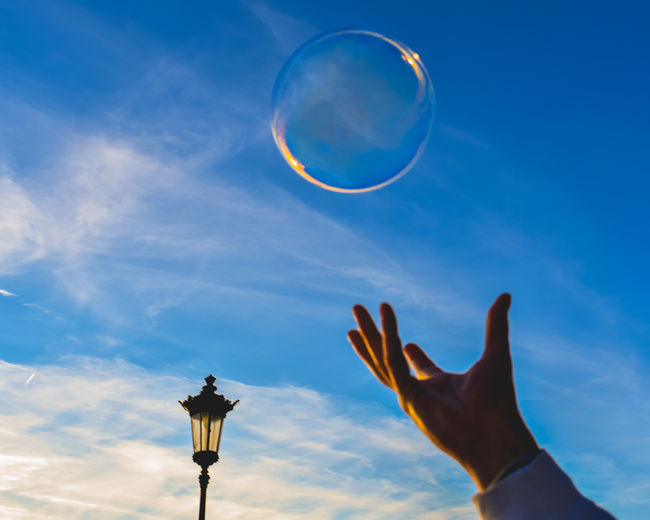 Close-up of person hand by bubble against sky