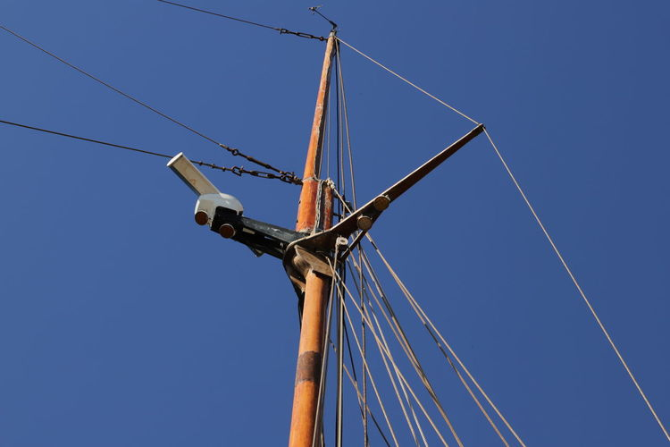 Low angle view of mast against clear blue sky