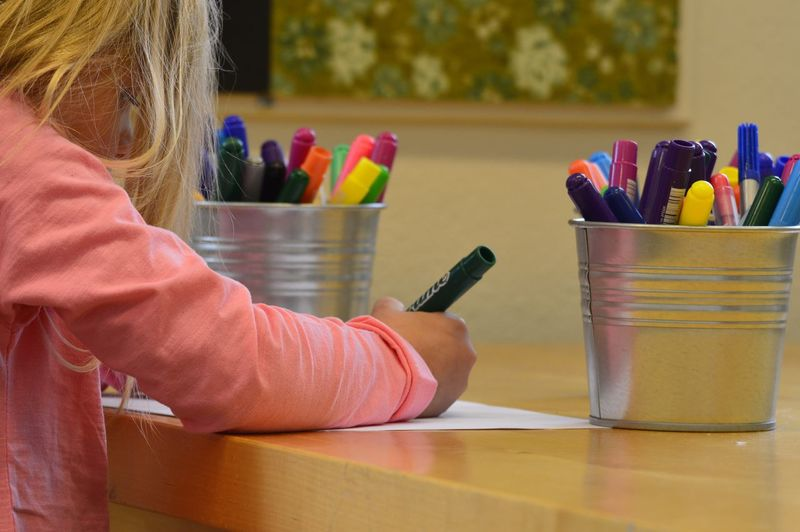 Side View Of Girl Drawing On Table At Home