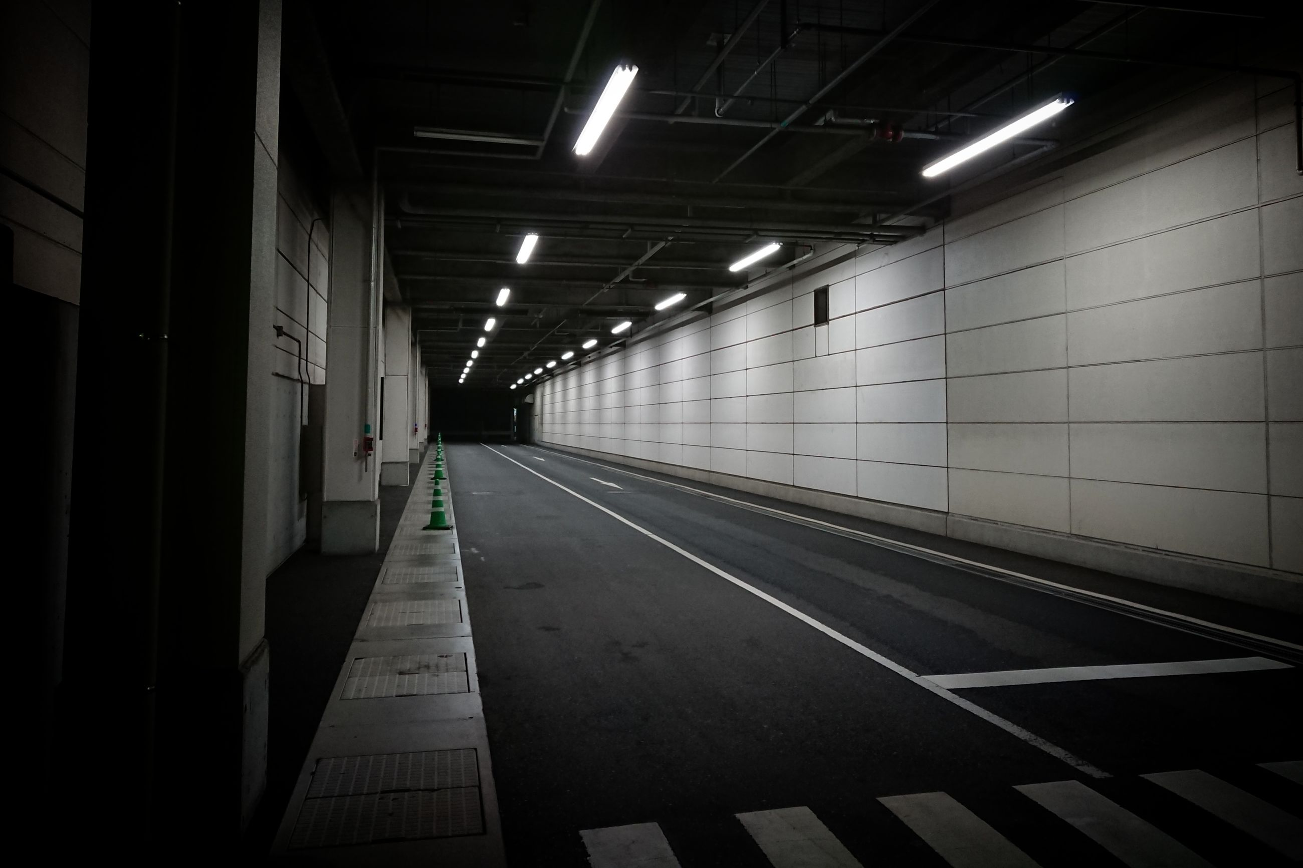 illuminated, lighting equipment, direction, transportation, architecture, indoors, empty, the way forward, public transportation, ceiling, subway, rail transportation, built structure, no people, diminishing perspective, wall - building feature, railroad station, flooring, railroad station platform, light, track, electricity, fluorescent light, architectural column, tiled floor, long, underpass