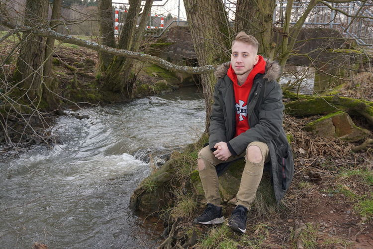 Portrait of man sitting by river in forest