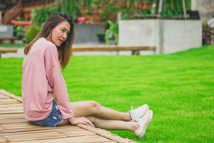 Woman looking away while sitting on field