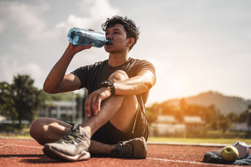 Full length of young man sitting at bottle against sky