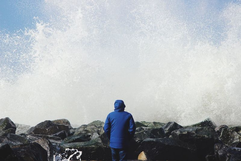 Rear view of person standing on rock while water splashing from sea against sky
