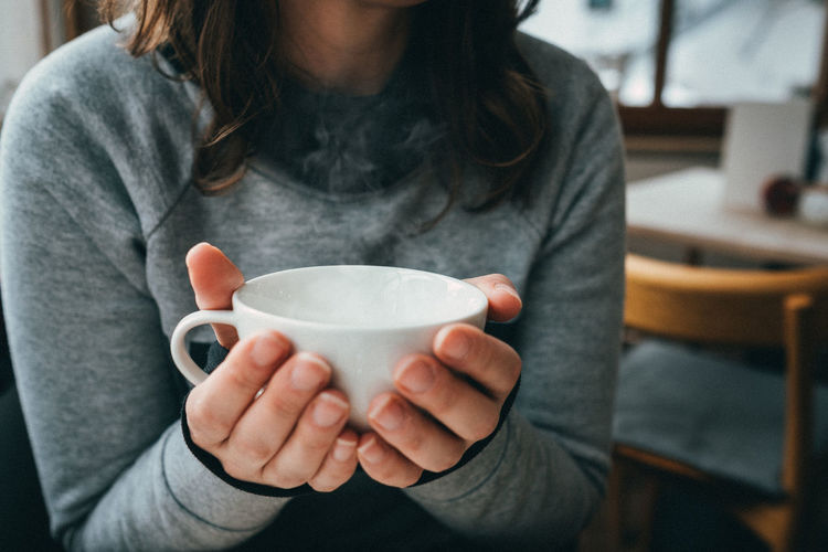 One Person Holding Drink Food And Drink Cup Focus On Foreground Mug Midsection Indoors  Lifestyles Woman Winter Cold Temperature Tea Tea Cup Tea - Hot Drink Hot Drink Drinking