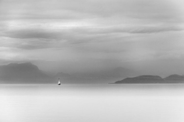 Boat sailing on sea against mountain and sky