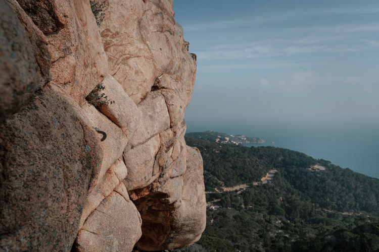 Scenic view of rock formation with climbing hooks by sea against sky
