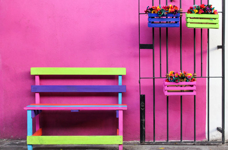 Colorful bench by potted plants on gate against wall