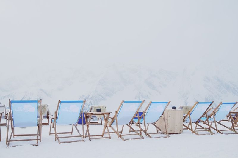 Chairs on beach against clear sky during winter