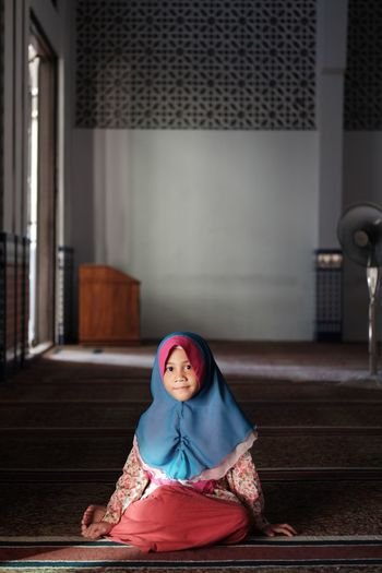 Portrait of girl in hijab sitting at mosque