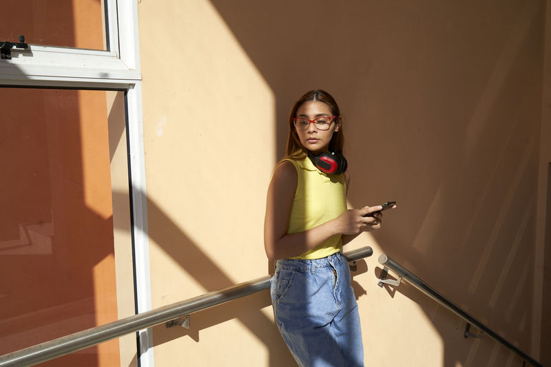 Young woman using phone while standing against wall