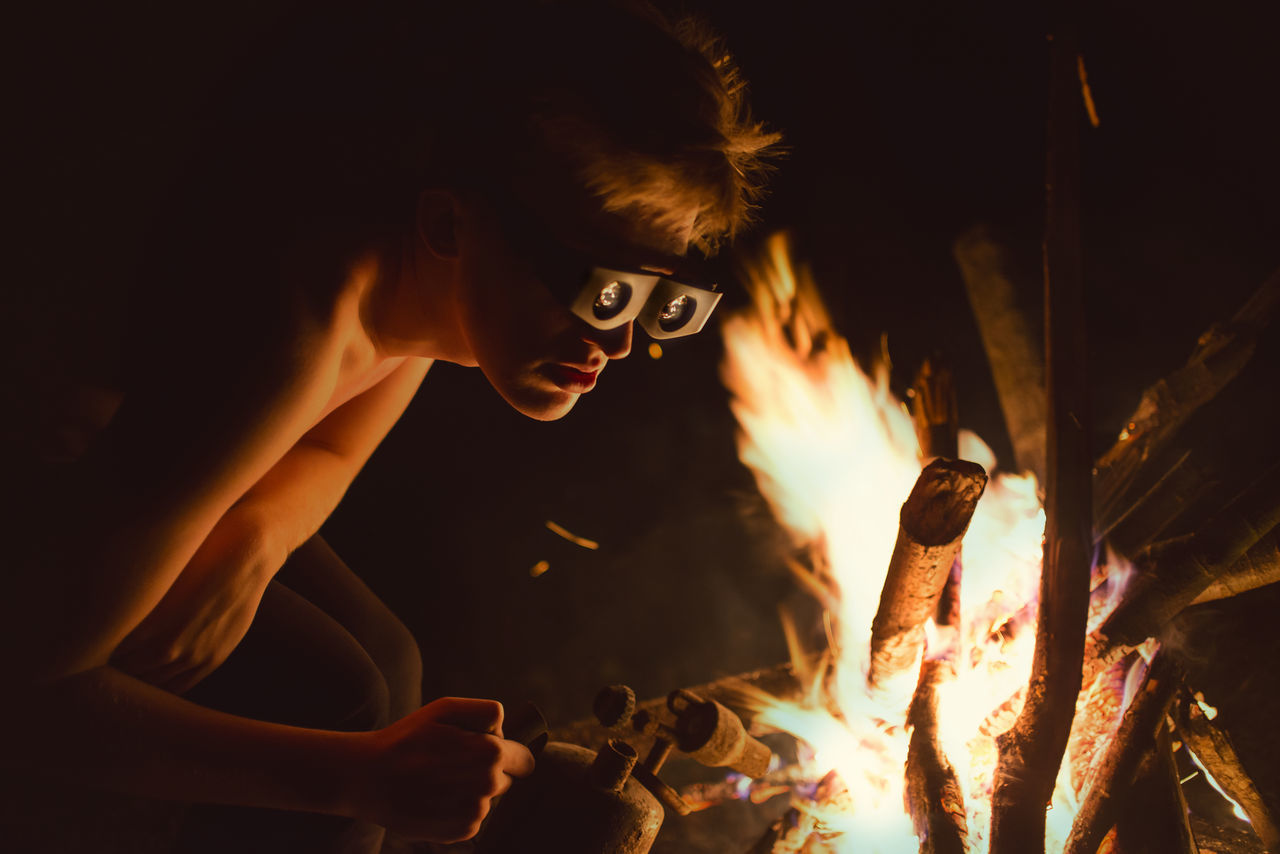 Shirtless Young Man Preparing Fire At Night