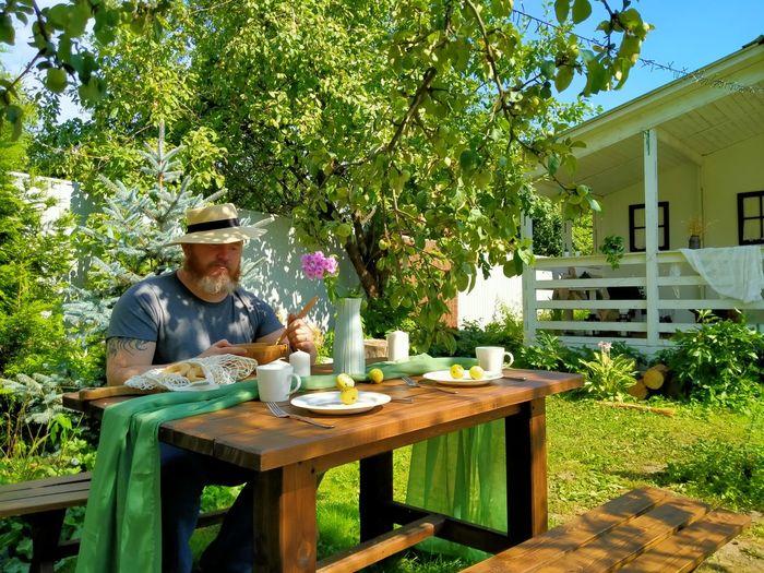 Man sitting on table at yard