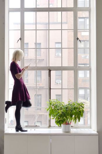 Side view of mature woman using mobile phone while standing on window sill