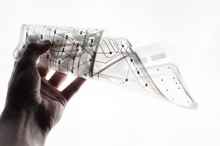 Close-up of hand holding transparent material against white background