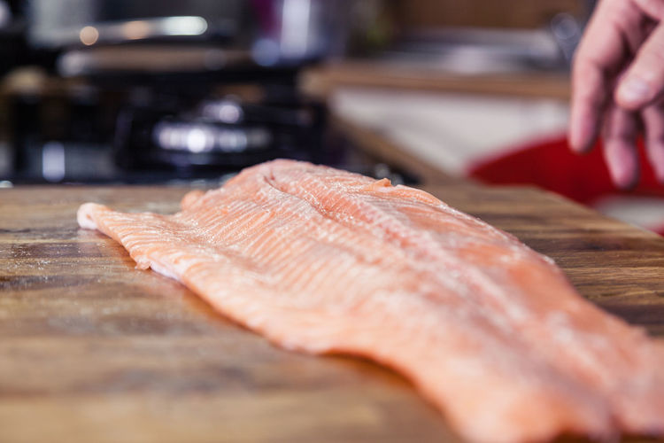 Cropped hand of man by fish on cutting board