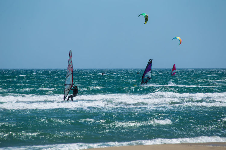 People kiteboarding and windsurfing against clear sky
