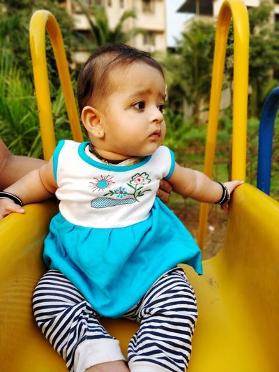 Cute Baby Girl Sitting On Slide In Park