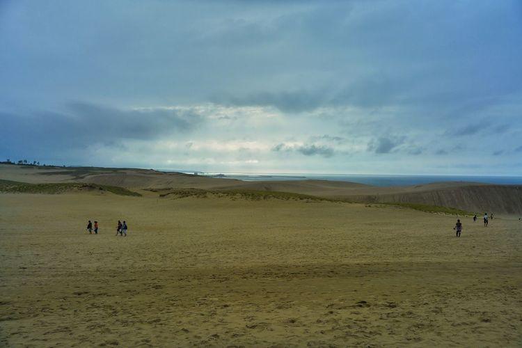 People walking on sand dune in desert against sky