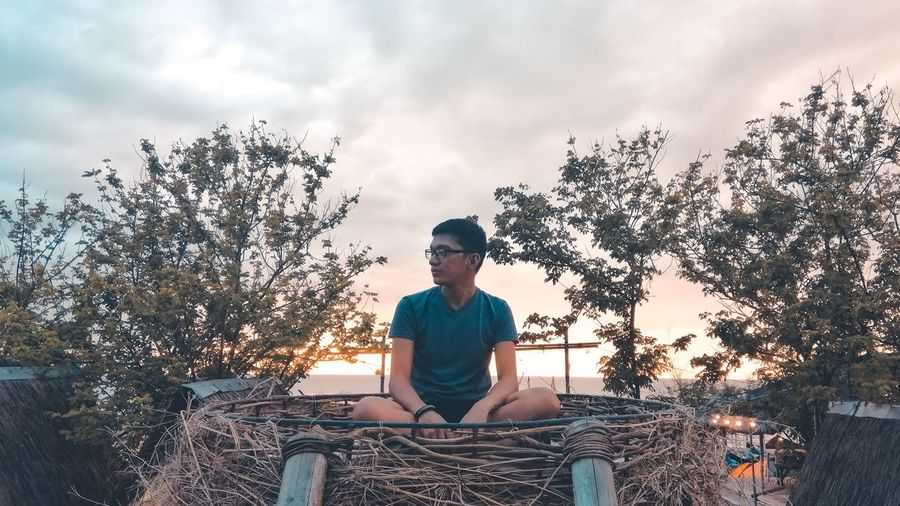Full length of man sitting on seat against sky