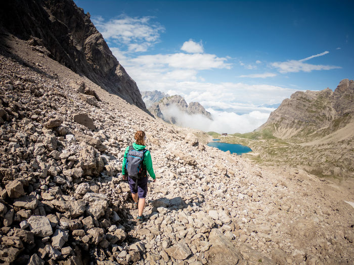 Woman hiking on rocky mountain during sunny day