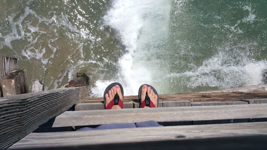 View of pier and womans feet in red flip flops sticking out over  ocean water