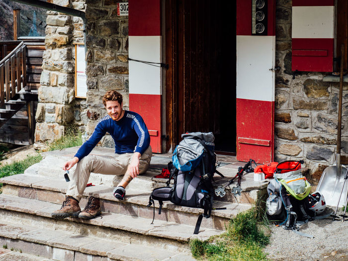 Young hiker sitting on steps at entrance of building
