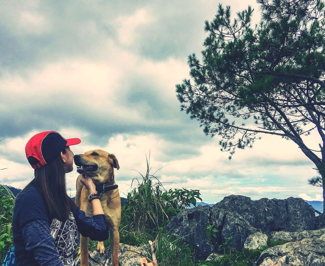 Woman with dog against sky