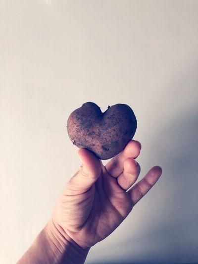 Cropped hand holding heart shape potato