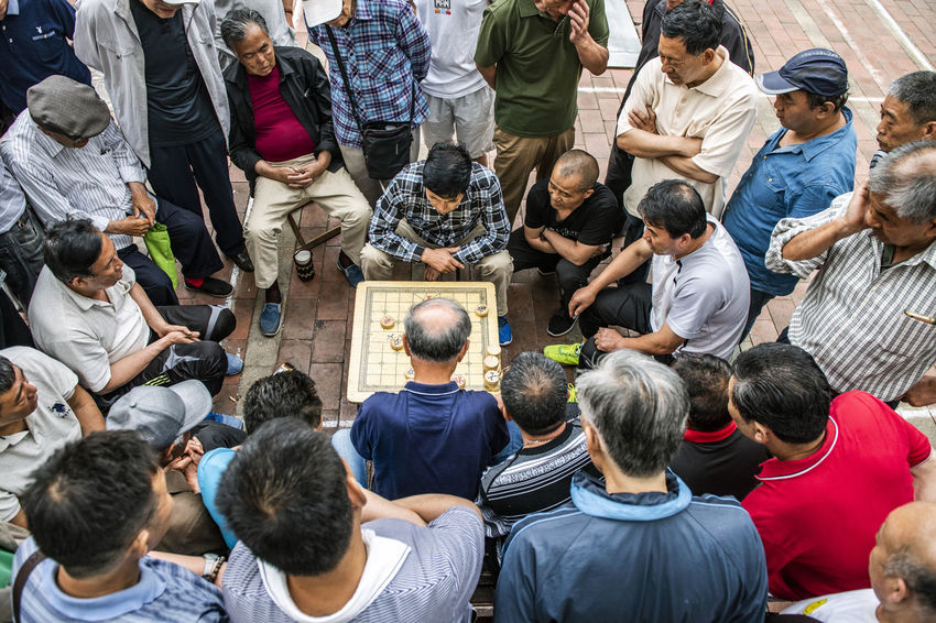 Above Adult Architecture Business Chinese Chess Communication Crowd Day Explaining  Game Group Of People High Angle View Large Group Of People Lifestyles Men Mixed Age Range Playing Real People Rear View Spectator Standing Togetherness