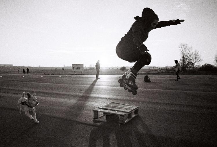 Full length of man running on skateboard against sky