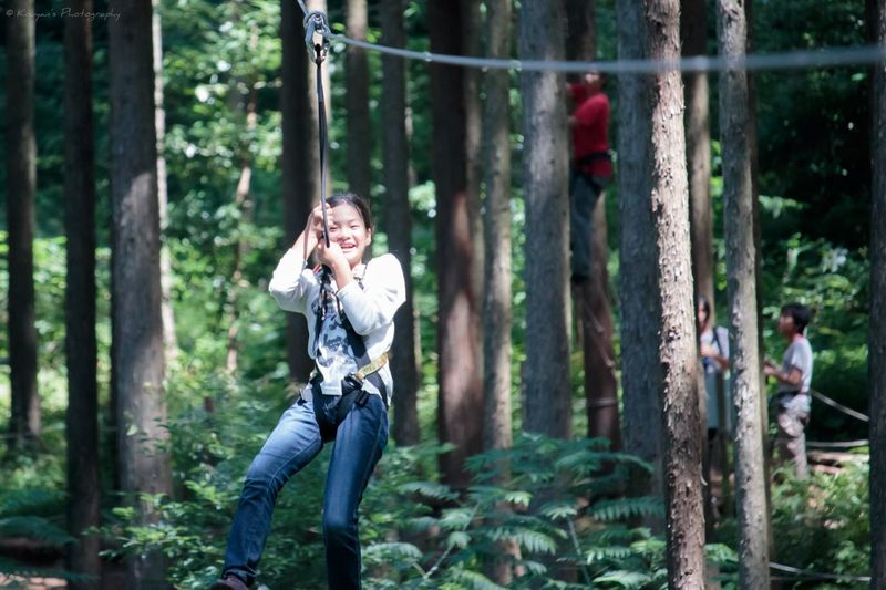 Girl riding zip line in forest