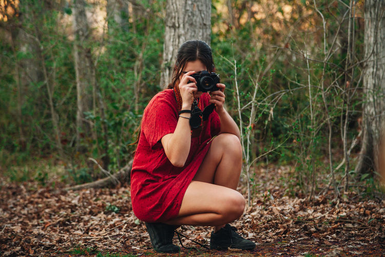 Young woman photographing in forest