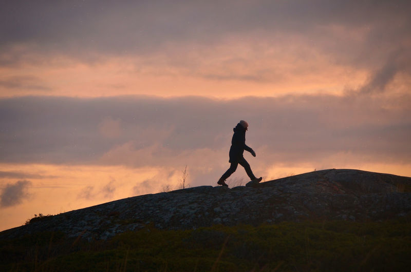 Woman walking on mountain against sky during sunset