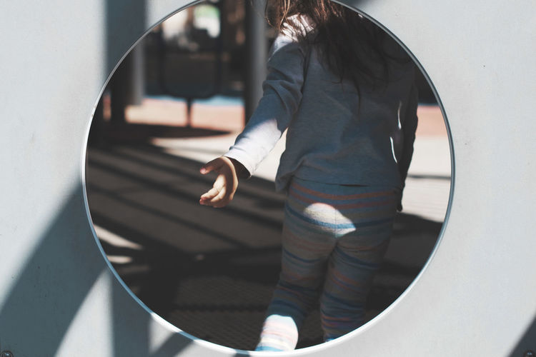 Rear View Of Girl Gesturing Seen Through Hole In Play Equipment