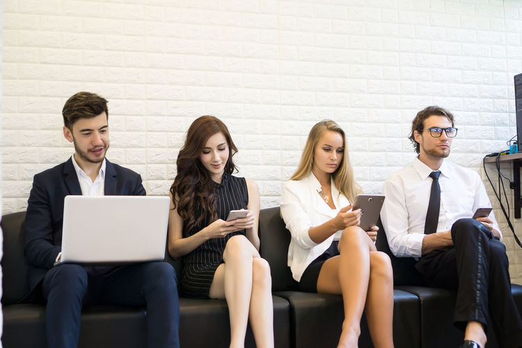 Business colleagues using technologies while sitting in office