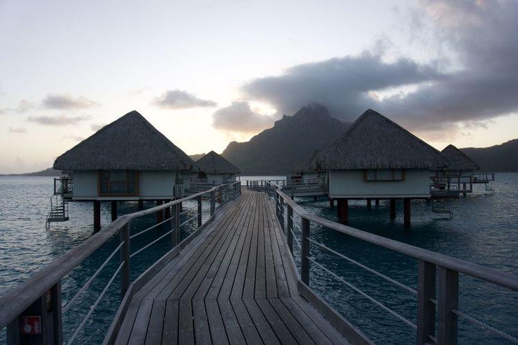 Pier leading towards tourist resort over sea