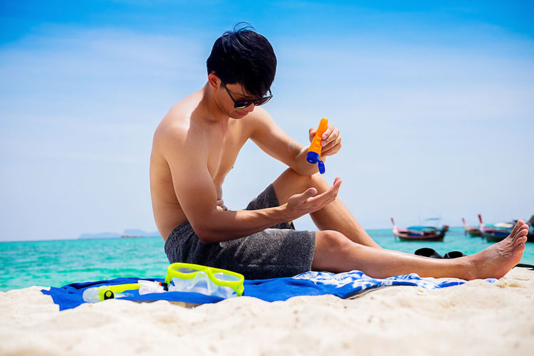Full length of man using sunscreen lotion while sitting at beach