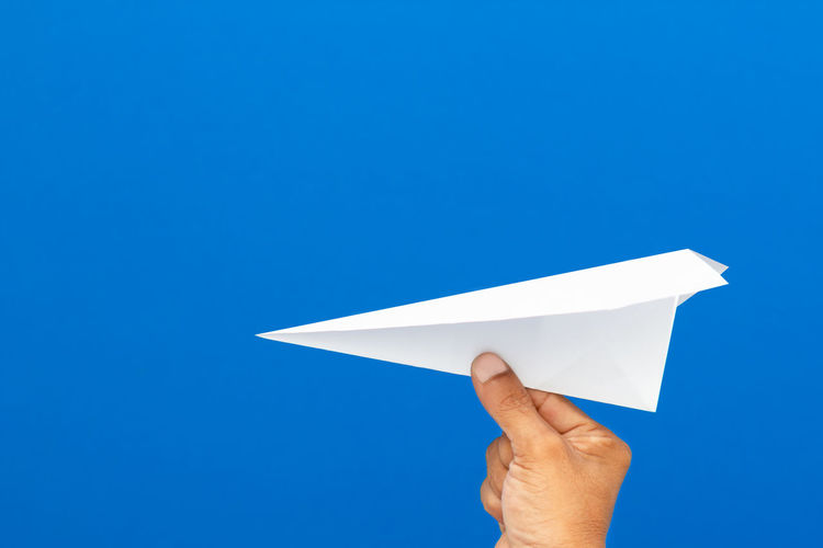 Person holding paper plane against blue background