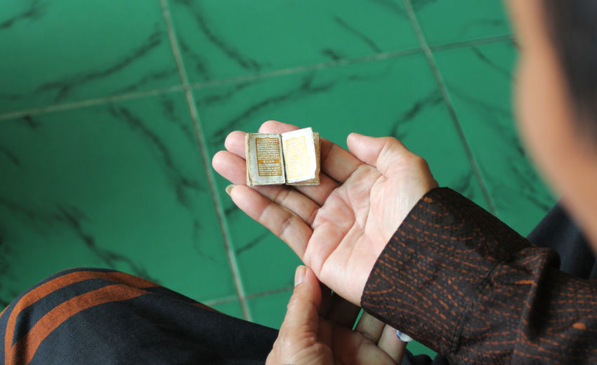 The world's smallest Qur'an belonging to Tubagus Tamyiz is 10 millimeters long and 10 millimeters wide and 5 millimeters thick and gold-inked. INDONESIA Ramadan  Smallest Al Quran Close-up Hand Human Hand Islam Koran Offbeat