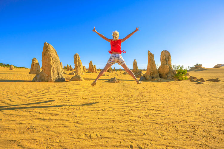 Rear view of woman with arms outstretched jumping against sky