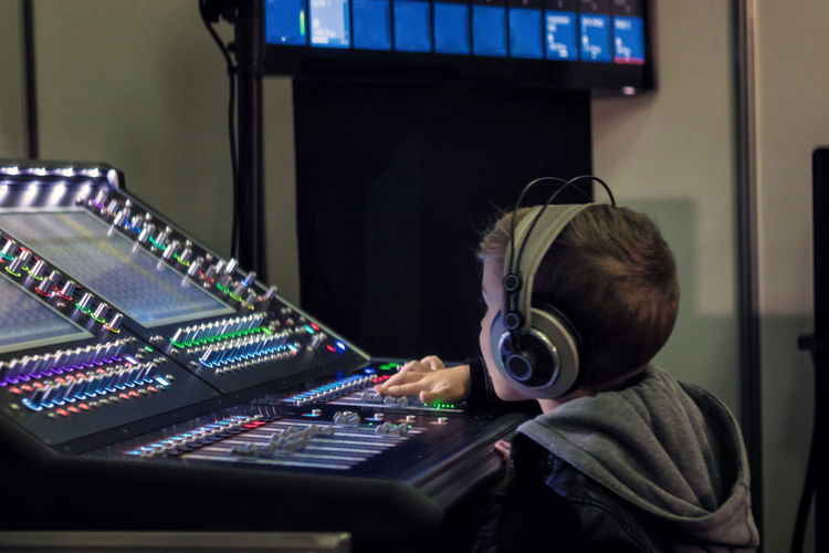 Close-up of boy using sound mixer in studio
