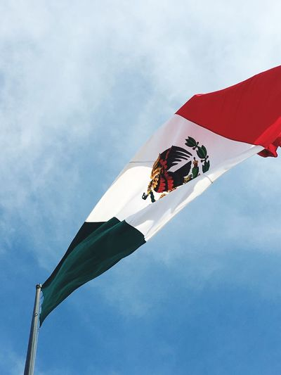 Low angle view of mexican flag against cloudy sky