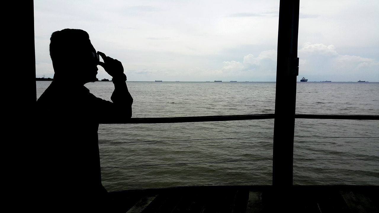 Side View Of Silhouette Man Standing In Boat Against Cloudy Sky