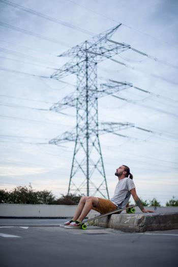 Full length of man sitting on electricity pylon against sky
