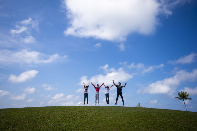 Happy children jump at the hill Sky Grass Group Of People Arms Raised Cloud - Sky Human Arm Togetherness Real People Field Friendship Limb Nature Women Land Day Lifestyles Leisure Activity Standing Arms Outstretched Adult Positive Emotion Human Limb 17.62°