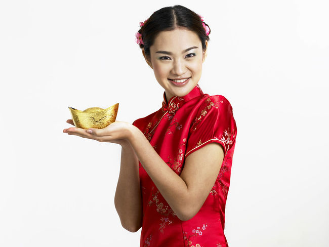 chinese woman holding gold ingot Gold Gong Xi Fa Cai New Year Prosperity Red Treasure Adults Only Cheongsam Chinese New Year Fortune Hair Bun Happiness Heritage Holding Looking At Camera One Person Only Women Portrait Qipao Smiling Studio Shot Toothy Smile Waist Up White Background Young Adult